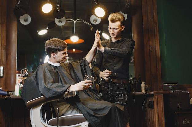 Uomo seduto su una sedia. parrucchiere con un cliente. guy beve un whisky. Foto Gratuite