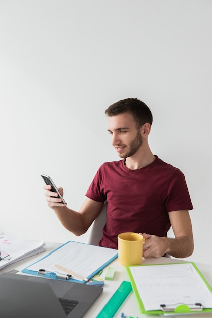 Man sitting on a chair and looking at his phone Free Photo