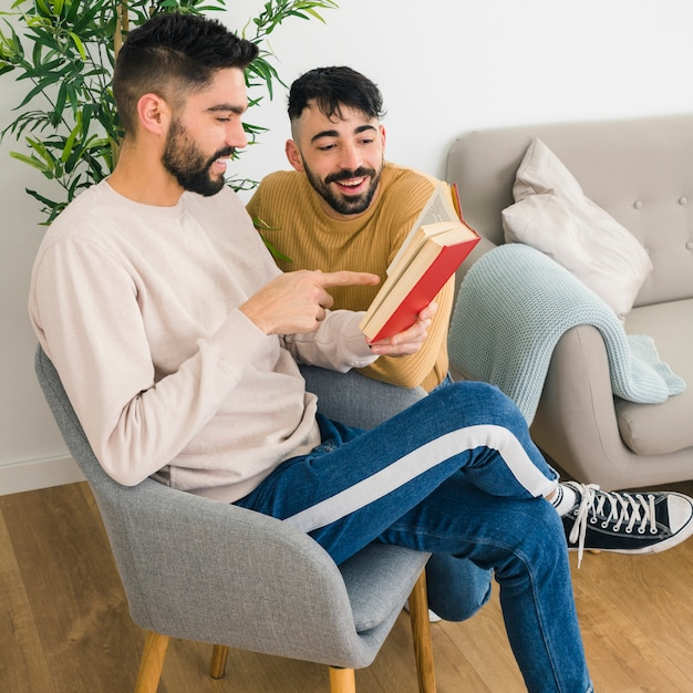 Two young male friends talking and chatting while sitting on chair at home | Photo: Freepik