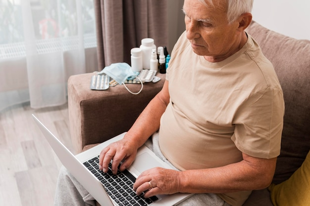 Man sitting on couch with laptop high angle Free Photo
