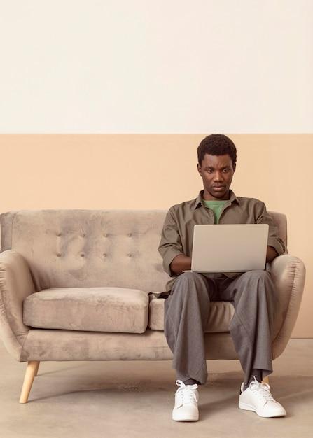 Uomo seduto sul divano e lavora Foto Gratuite