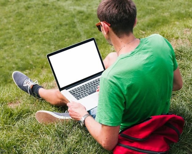 Man sitting on the grass holding laptop Free Photo