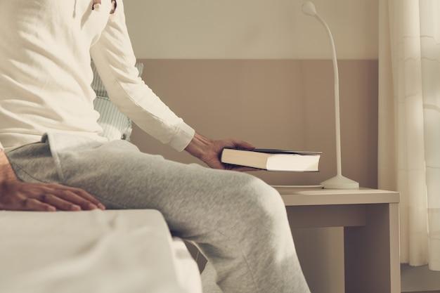 스탠드에 책을 남기고 침대에 앉아있는 남자 프리미엄 사진