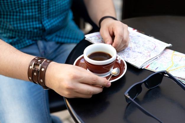 Человек сидит в кафе с чашкой кофе и картой Premium Фотографии