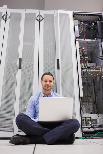 Man sitting in front of servers with his laptop Premium Photo