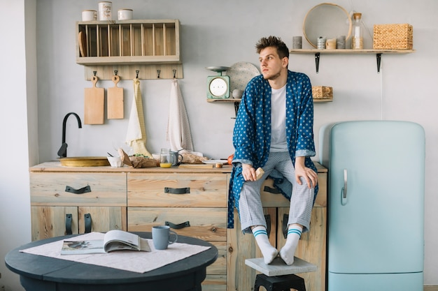 Man sitting on kitchen counter holding food Free Photo