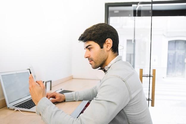 Man sitting at laptop using smartphone Free Photo