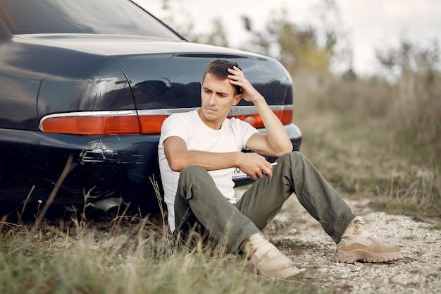 Man sitting near the  broken car Free Photo