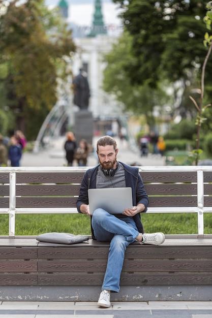 Человек сидит на скамейке и работает на ноутбуке Бесплатные Фотографии
