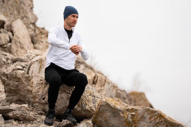 Человек сидит на скалах в природе Бесплатные Фотографии