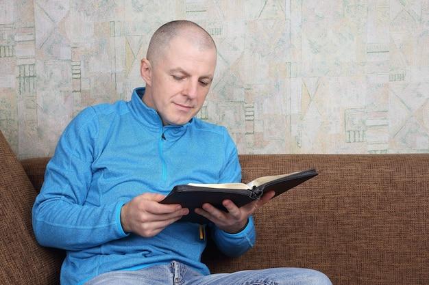 소파에 앉아 성경 책을 읽는 남자 프리미엄 사진