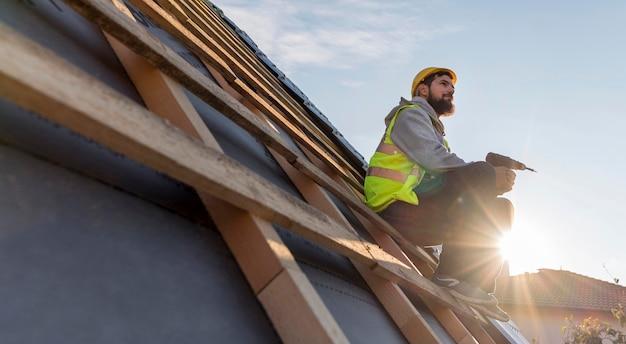 日光の下で屋根に座っている男 Premium写真