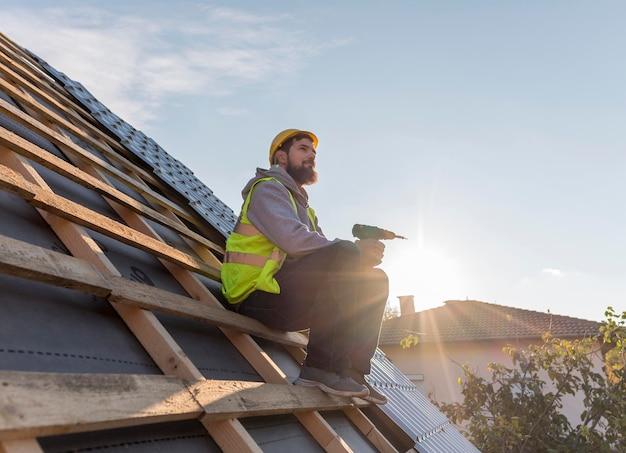 屋根の上に座っている男 無料写真