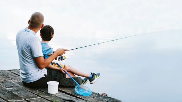 Man sitting on pier with his son fishing on lake Free Photo