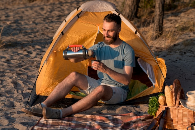 Man sitting and pouring from thermos Free Photo