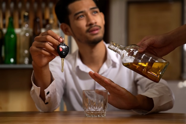 The man sitting in restaurant holding the car key refusing alcohol from his friend. Premium Photo