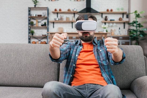 Man sitting on sofa wearing virtual reality glasses driving the car Free Photo