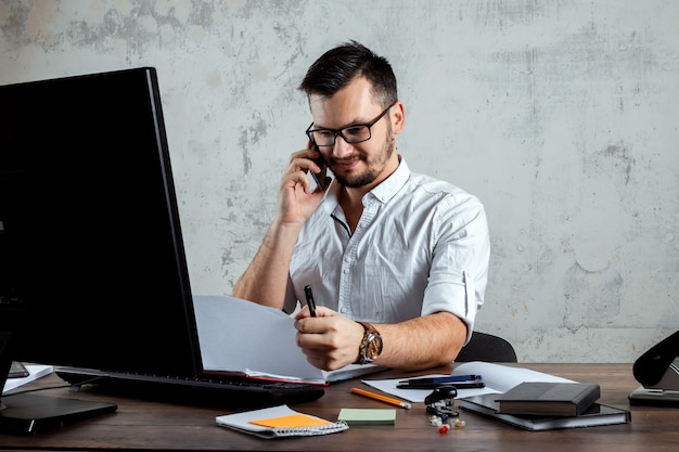Man sitting at a table in the office, talking on the phone, decides an important question. the concept of office work, a startup. copy space. Premium Photo