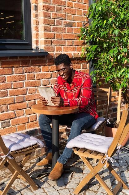 Uomo seduto a un tavolo e leggere Foto Gratuite