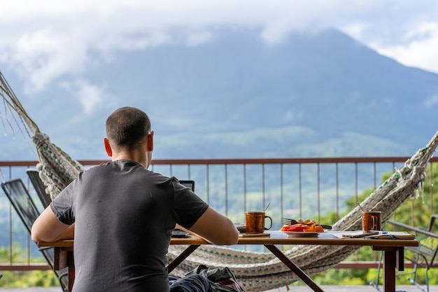 Man sitting on a table with breakfast while working with a view of a volcano in front of him. costa rica Premium Photo