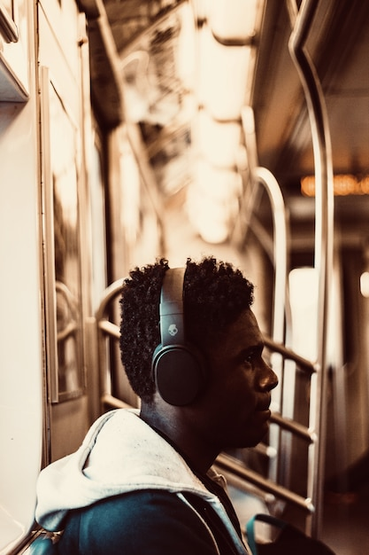 Man sitting and wearing headphones inside train Free Photo