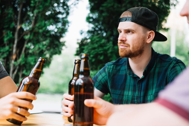 Man sitting with his friend holding brown beer bottle Free Photo