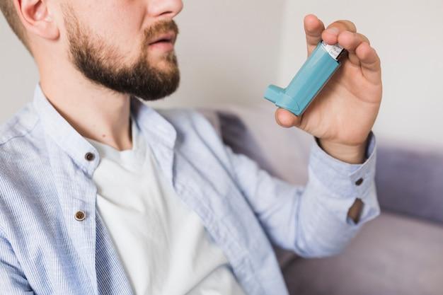 Man sitting with inhaler Free Photo