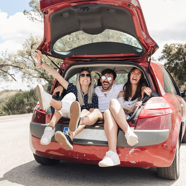 Man sitting with two female friends in the car trunk Free Photo