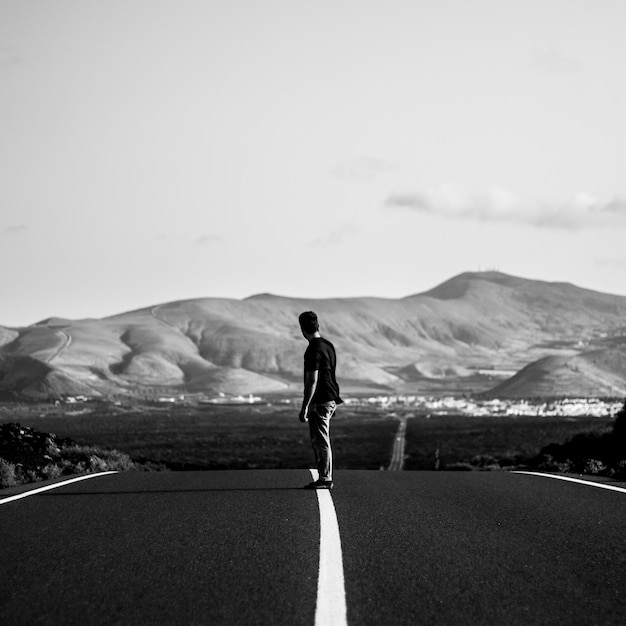 Uomo su uno skateboarder in sella su una strada statale vuota con incredibili colline Foto Gratuite