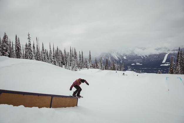 Человек, катающийся на лыжах на снежных альпах на горнолыжном курорте Бесплатные Фотографии