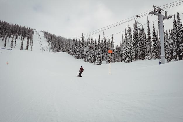 Uomo che scia sulle alpi innevate nella stazione sciistica Foto Gratuite