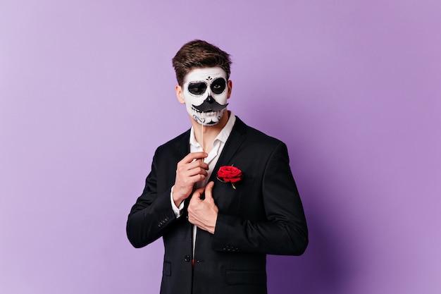 L'uomo con la maschera da teschio strizza l'occhio civettuolo, posando con i baffi sovrapposti per il ritratto su sfondo isolato. Foto Gratuite