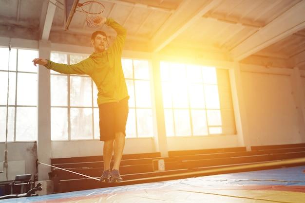 Человек расслабляется, гуляя и балансируя на веревке, слеклайн в спортивном зале Premium Фотографии