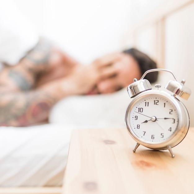 Man sleeping with alarm clock on wooden desk Free Photo