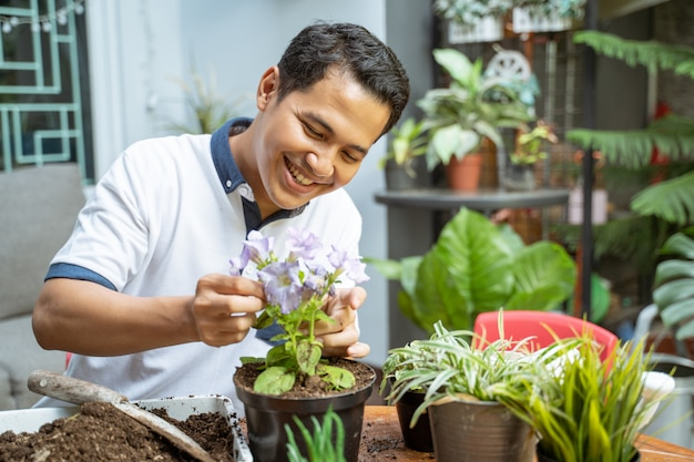 Man smiled happily holding flower plants in pots while taking care Premium Photo