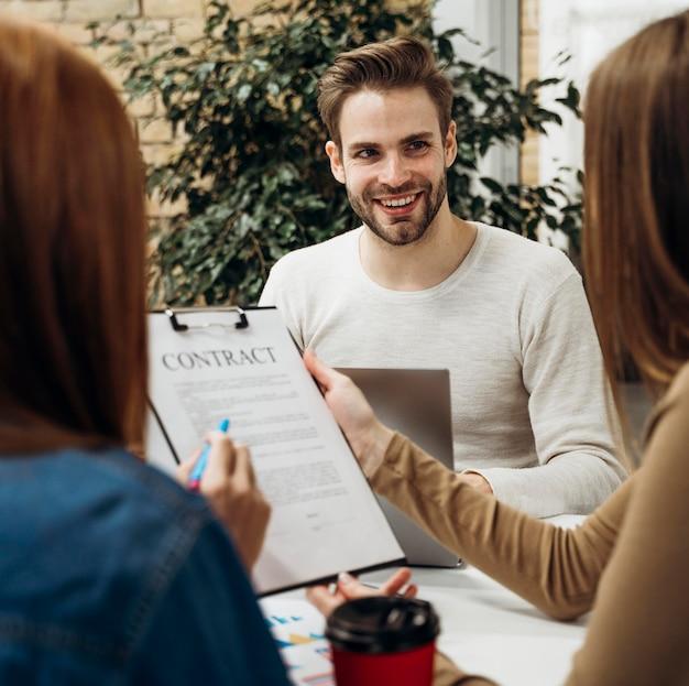 Мужчина улыбается коллегам на встрече Бесплатные Фотографии