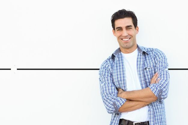 Man smiling leaning against a white wall Free Photo