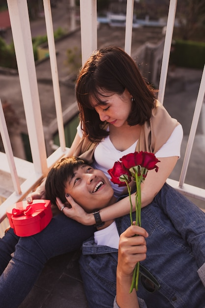 Man smiling lying on the legs of a woman with a bouquet of roses Free Photo