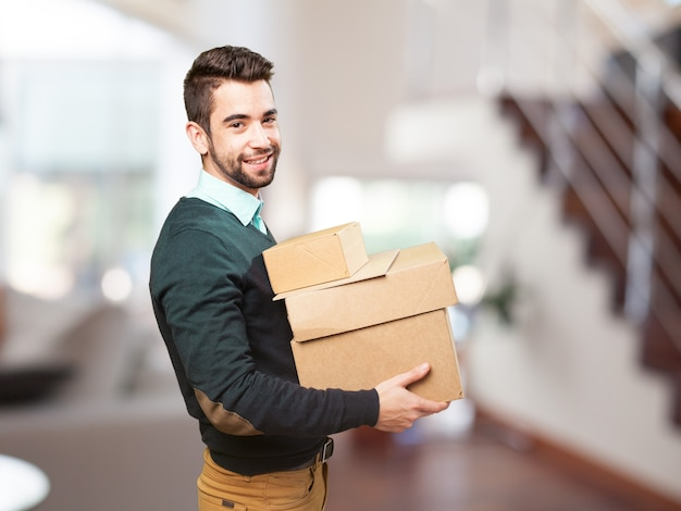 Man smiling with a lot of boxes Free Photo