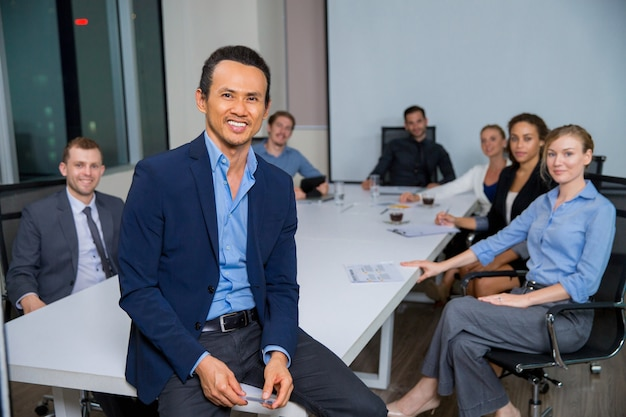 Man smiling with suit sitting at a table with colleagues behind Free Photo