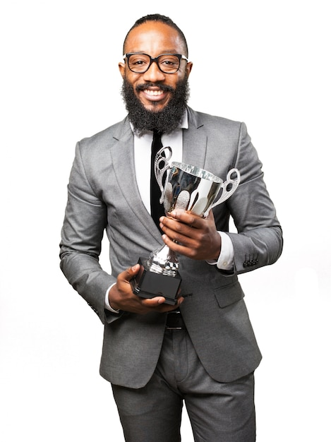 Man smiling with suit and trophy Free Photo