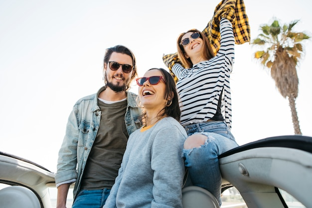 Man and smiling women with upped hands leaning out from car Free Photo