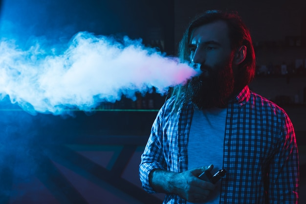 A man smokes a cigarette and lets out smoke in a nightclub. Premium Photo