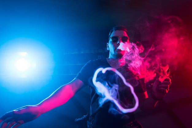 A man smokes a cigarette in a nightclub. Premium Photo