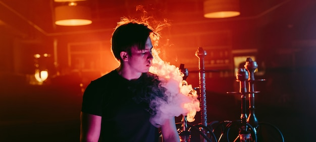 Man smokes a hookah and lets out a cloud of smoke Premium Photo