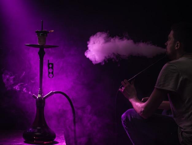 The man smoking the classic shisha. beautiful  colored rays of light and smoke. the concept of hookah smoking. Free Photo