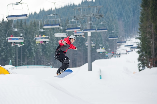 Man on the snowboard jumping over the slope in winter day Premium Photo