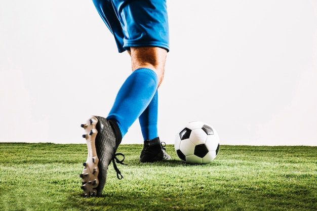 Man in soccer boots kicking ball Free Photo