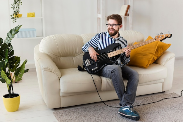 Free Photo | Man on sofa at home playing electric guitar