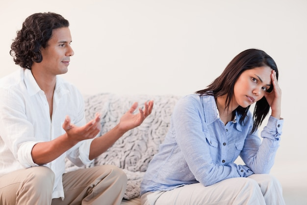 Man on the sofa trying to apologize to his girlfriend Premium Photo